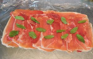 Lägg ut skinkan på plastfilm och fördela salvian över